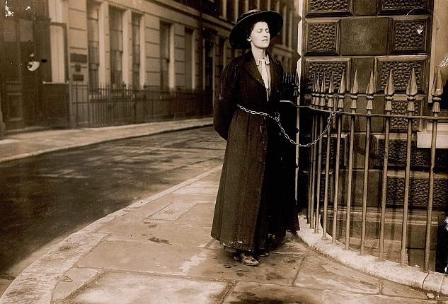 A suffragette chaining herself to railings in protest in the early 1900s-web.
